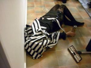 En kvinna ligger på ett golv med en jacka på huvudet. Hon håller i en ölburk. Bredvid henne ligger en dammsugare.