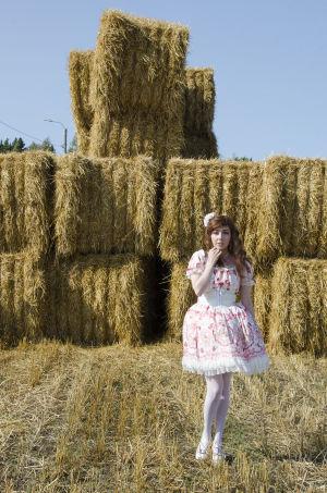 En kvinna klädd i så kallade Lolitakläder - en fluffig vit och rosa klänning med spetsar på. Hon har vita högklackade skor och blommor i håret. Hon står framför en massa höbalar.