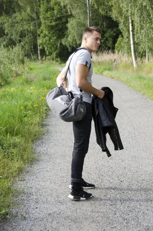 En man iklädd svarta jeans och en grå t-skjorta står på en grusväg kantad med grönt gräs och blommor. Han har ryggen snett mot betraktaren och tittar på något till sidan.