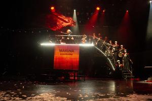 Marine Teräväkynä (Katariina Kaitue) liehuttaa punaista lippua korokkeella, jossa lukee: Marina presidentiksi.