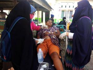 Kvinna som skadats i jordskalvet i Donggala får första hjälp.