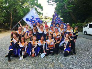 Ett yosakoi danslag i Japan. Alla är kvinnor och de bär vita och blåa dräkter. Två av dem håller i stora flaggor som också går i vitt och blått.