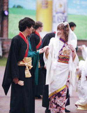En man och en kvinna som utför den japanska dansen yosakoi. Hon är iklädd vit kimono och han en svart. De håller varandra i handen och ler.