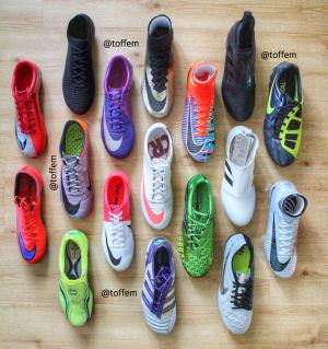 Flera fotbollsskor sedda uppifrån. De är av olika färger och märken - utradade på ett trägolv.