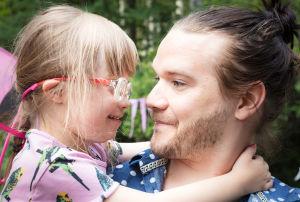 Laila on Heikki-isän sylissä ja katsoo Heikkiä suoraan silmiin.
