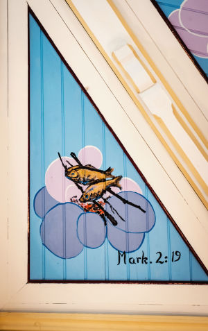 Kaloja grillattavina maalattuna kirkon kattoon