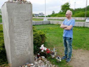 Aktivisti Kamil Mrozowicz seisoo joukkomurhattujen juutalaisten muistomerkillä Jedwabnessa