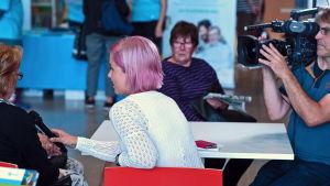 Nettiä ikä kaikki -kampanjan kirjastokiertueella Espoossa: Päivikki Koskinen haastattelee kävijää Ylen Puoli Seitsemän -ohjelmaan.