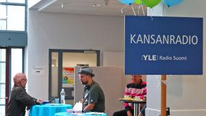 Nettiä ikä kaikki -kampanjan kirjastokiertueella Joensuussa: Kansanradion toimittaja Olli Haapakangas juttelee kävijän kanssa.