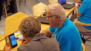 Nettiä ikä kaikki -kampanjan kirjastokiertueella Kajaanissa: Paikallinen vertaisneuvoja opastaa kävijää kännykän käytössä.