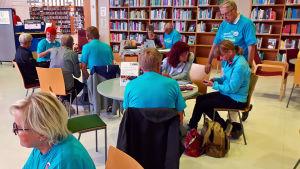 Nettiä ikä kaikki -kampanjan kirjastokiertueella Kuopiossa: Savonetin ja muiden järjestöjen vertaisopastajia auttaa kävijöitä.