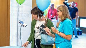 Nettiä ikä kaikki -kampanjan kirjastokiertueella Turussa: SeniorSurf-toiminnan Liisa Tiainen esittelee kävijälle tabletin käyttöä.