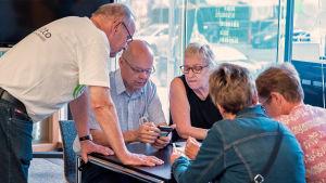 Nettiä ikä kaikki -kampanjan kirjastokiertueella Turussa: Paikallisia vertaisopastajia ja kävijöitä pöydän ääressä kännykän kanssa.