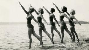 Suomi-Tytöt poseeraavat rantakalliolla.