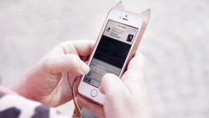 Kännykkä lähikuvassa käsissä