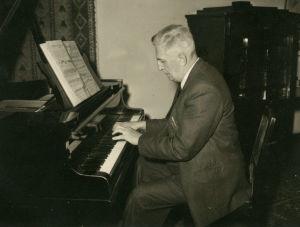 Professori Ernst Linko soittaa flyygeliä.