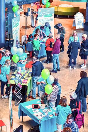 Nettiä ikä kaikki -kampanjan kirjastokiertueella Espoossa. Sellon kirjaston aulan yleisnäkymä: esittelypöytiä ja yleisöä.