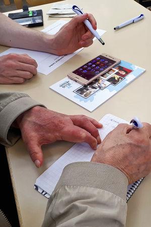 Nettiä ikä kaikki -kampanjan kirjastokiertueella, miehen kädet tekevät muistiinpanoja paperille.