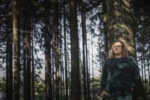 Riia Puska metsässä, nojaa puuta vasten.