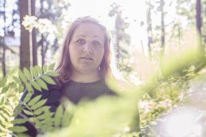 Riia Puska metsässä, etualalla pihlajan lehtiä epätarkkana.
