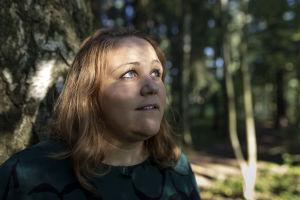 Riia Puska metsässä, nojaa puuta vasten, katsoo yläviistoon.