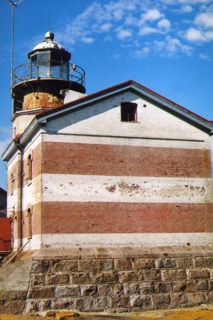 Vanha kuva kuluneesta, punavalkoraidallisesta majakasta.