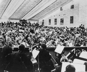 Meri Louhos istuu orkesterin keskellä Taikahuilun esityksessä Savonlinnan oopperajuhlilla.