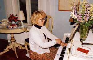 Meri Louhos soittaa Suomalaisten valkoisella pianolla.