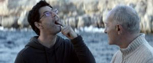 Christos (Sakis Rouvas) esittelee hampaassaan olevaa paikkaa isännälle (Giorgos Kentros) elokuvassa Chevalier