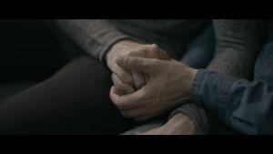 Kaksi miestä pitää toisiaan kädestä, lähikuva käsistä