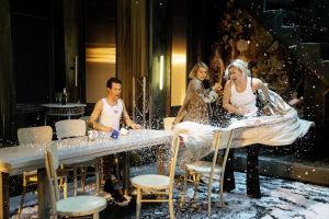 Emmi Parviaisen näyttelemä Maša kiskaisee pöytäliinan pois juhlapöydästä. Pöydän ääressä myös Tuzenbach (Olavi Uusivirta) ja Irina (Marja Salo).