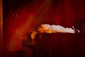 Maša (Emmi Parviainen) makaa pianon päällä, tulipalon riehuessa taustalla.