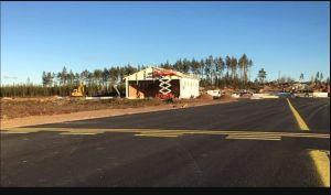 En halvklar stor förvaringshall står bredvid en tom landningsbana.