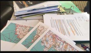En hög med olika papper på ett bord. Det synns papper med text och olika kartor.