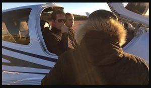 Två män sitter inne i styrhytten på ett litet flygplan. Framför dem står någon klädd i en svart rock med ryggen vänd mot kameran.