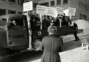 """Koululaisia kuorma-auton lavalla kädessään iskulausekylttejä: """"Romuista aseita ja ammuksia rintamalle."""""""