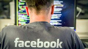 Mies tietokoneen edessä selkä kuvaan päin. Puserossa lukee Facebook.