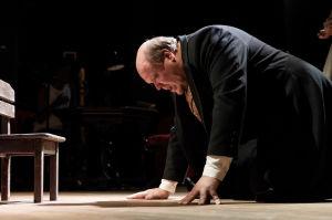 Hannu-Pekka Björkmanin näyttelemä Fjodor Karamazov polvillaan lattialla.
