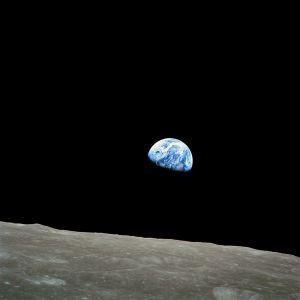 """Fotografiet """"Earthrise"""" med jorden som stiger över månslätten."""