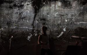 Ivan Karamazov (Miro Lopperi) seisoo pimeydessä, harmaan seinän edessä, johon on kirjoitettu sanoja ja nimiä.