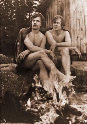 Kaksi miestä istuu nuotion äärellä ilman vaatteita.