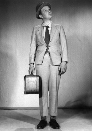 Lasse Pöysto seisoo suorana mustavalkoisessa kuvassa. Hänellä on kädessään matkalaukku ja hän katsoo hieman yläviistoon.