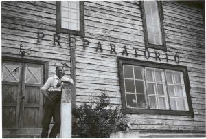 Svartvit bild: man står och lutar mot dörrpost utanför trähus. På väggen texten PREPARATORIO.