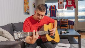 Reumaa sairastava Olli Mäkelä soittaa kitaraa sohvalla