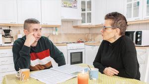 Poika ja äiti, Olli ja Asta Mäkelä keittiön pöydän ääressä