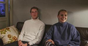 Ung man i vit polotröja och ung kvinna i blå collegetröja sitter bredvid varann i en soffa.
