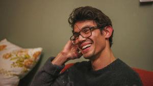Ung, mörkhårig man med glasögon skrattar i en röd soffa, i bakgrunden en grönmålad vägg.