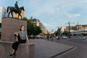 Nuori nainen istuu Mannerheimin patsaan juurella