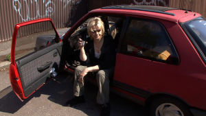 Helena Třeštíkován dokumentin Mallory päähenkilö istuu autossa ja juo kahvia.