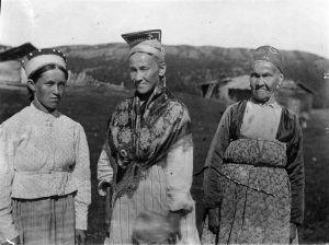 Svartvitt fotografi av tre kvinnor i traditionella skoltsamiska dräkter med speciella huvudbonader.